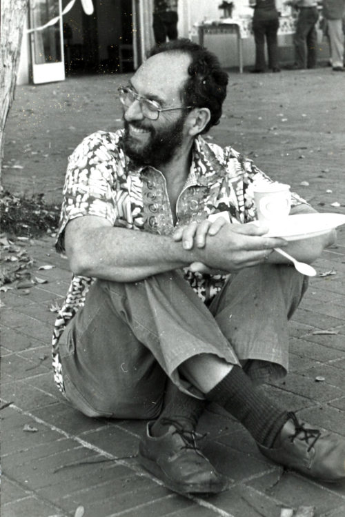 Sheldon Margen sitting on the ground, cross legged and smiling to his right